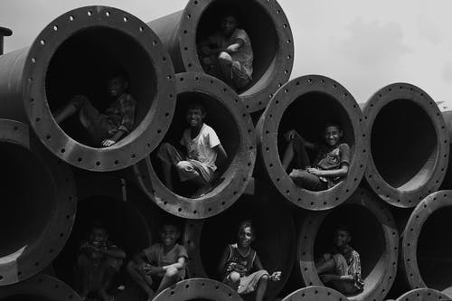 Grayscale Photo of People in Round Hole