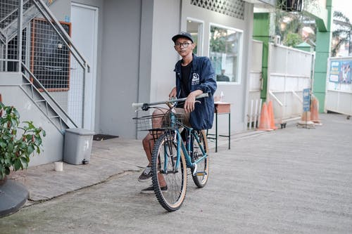 Man in Blue Jacket Riding on Blue Bicycle