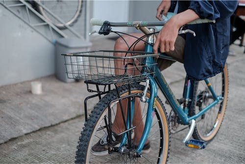 Person in Blue Long Sleeve Shirt Sitting on Blue Bicycle