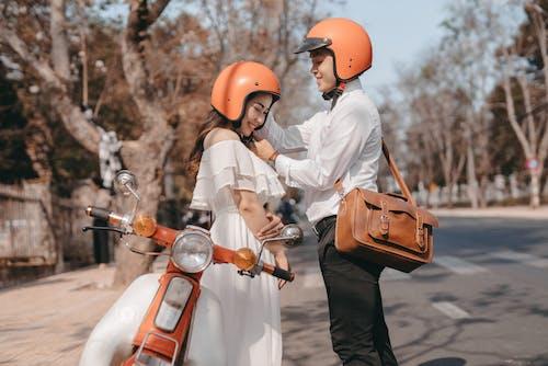 Man in White Long Sleeve Shirt Wearing Orange Helmet Standing Beside a Woman in White Dress