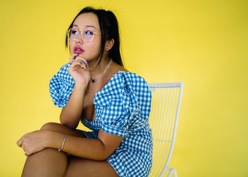 Woman in Blue and White Checkered Button Up Shirt Sitting on Bed