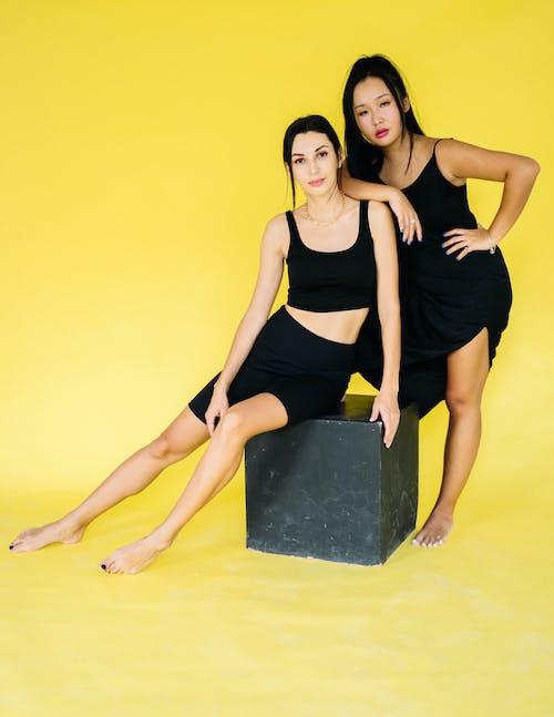 Kobieta W Czarnym Podkoszulku I Czarnej Spódnicy Siedzi Na Czarnym Pudełku
