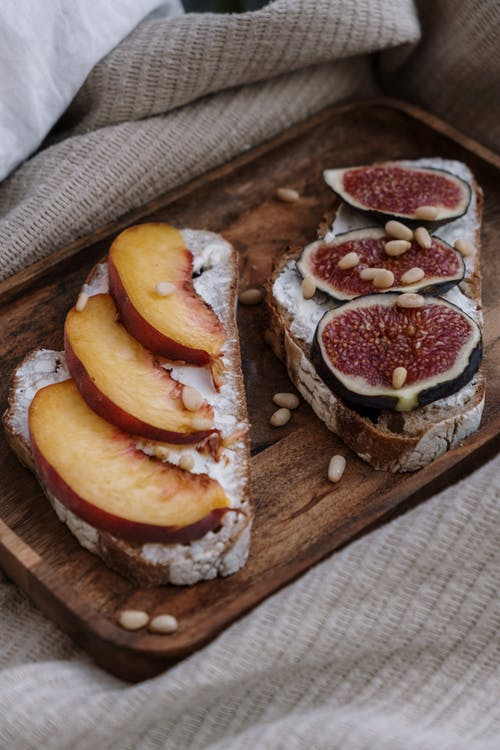 Sliced Bread With Sliced Orange Fruit on Brown Wooden Chopping Board