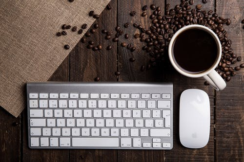 Flat Lay Photography of Apple Magic Keyboard, Mouse, and Mug Filled With Coffee Beside Beans