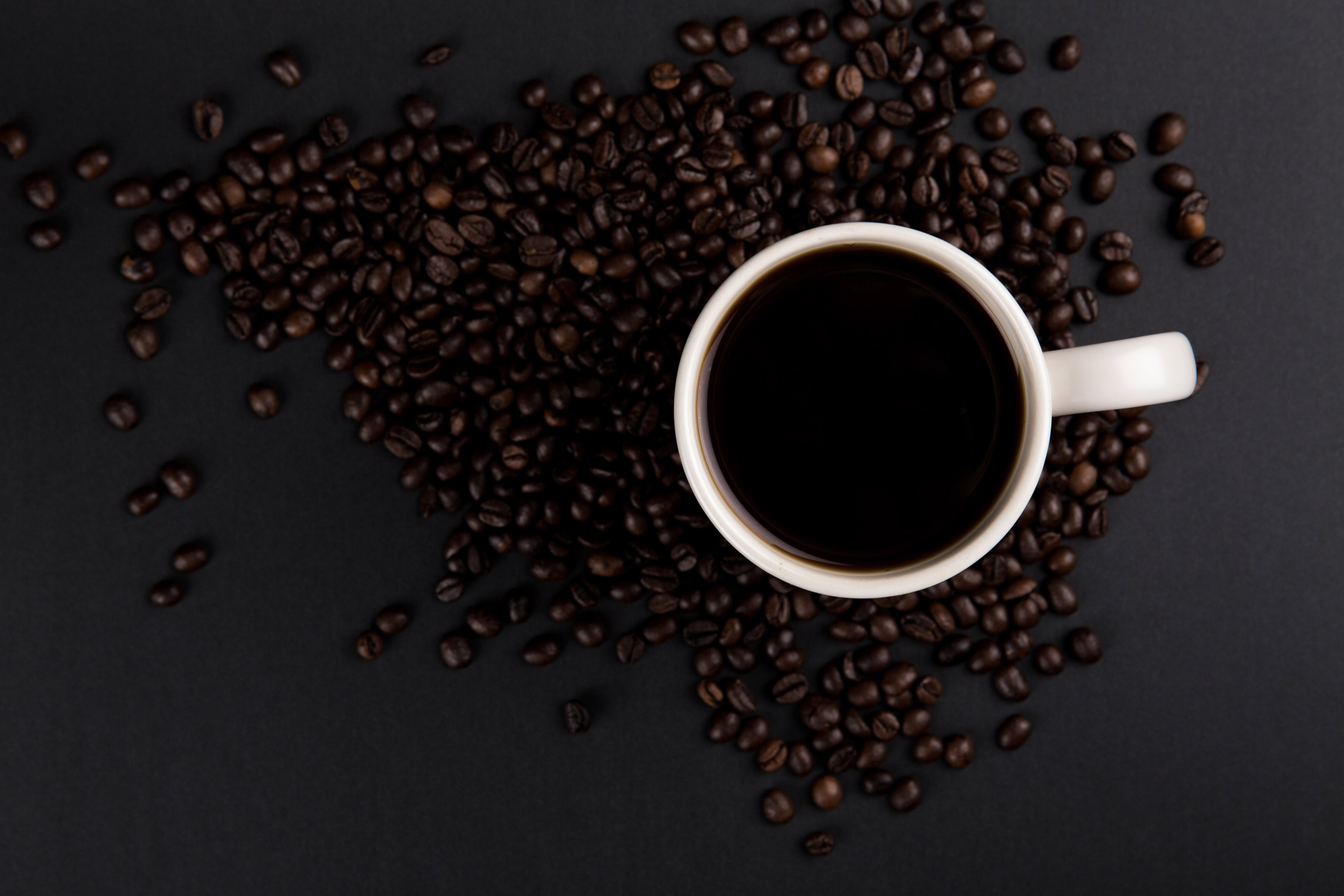 Flat Lay Photography of Cup of Coffee Surrounded by Coffee Beans