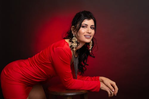 Side view of positive female with makeup leaning on wooden stool and looking at camera