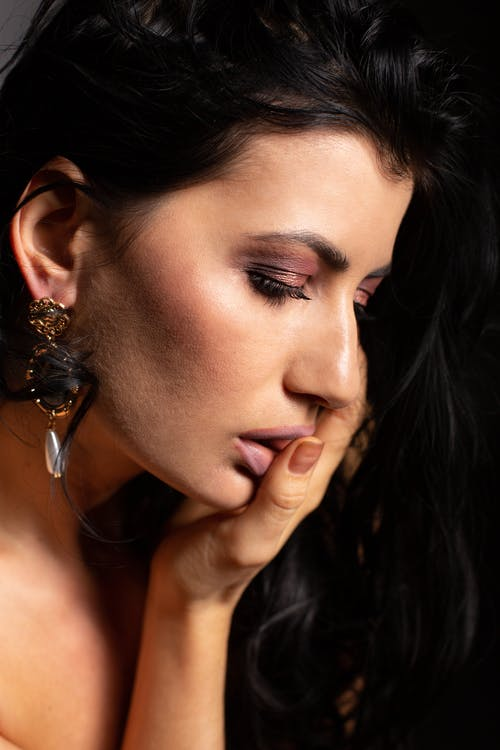 Upset woman with makeup in earring