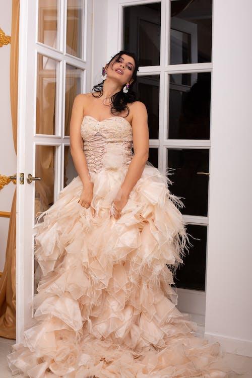 Elegant woman in stylish dress standing near door