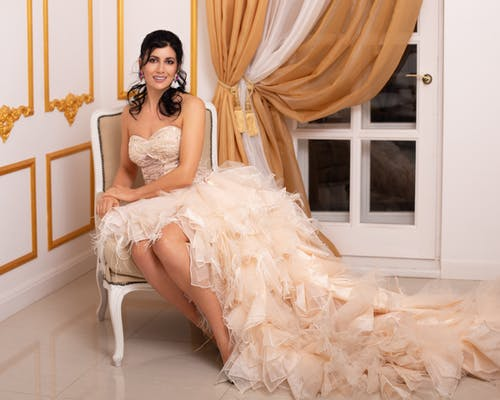 Full body of elegant female in fancy dress with long hem looking at camera while sitting on chair in room near door with curtain