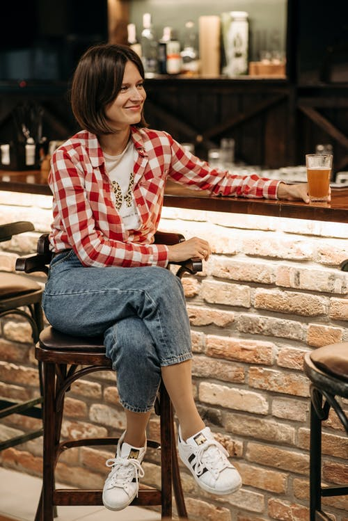 Woman in Red and White Plaid Dress Shirt and Blue Denim Jeans Sitting on Brown Wooden