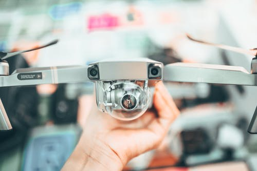 Crop unrecognizable person holding modern drone in hand and demonstrating camera against blurred interior background
