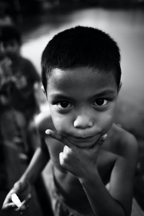 Grayscale Photo of a Topless Boy Looking at the Camera