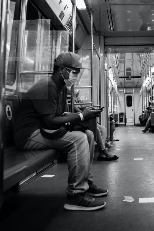 Grayscale Photo of a Man Using His Cellphone in the Train
