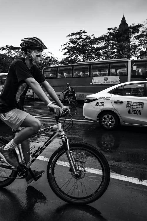 Grayscale Photo of a Cyclist on the Road