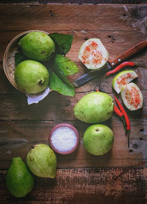 Sliced Green Fruit Beside Red Handled Knife on Brown Wooden Table