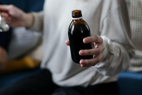 Fotos de stock gratuitas de botella, jarabe para la tos, mano