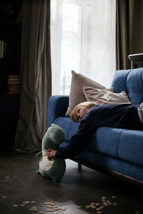 Woman in Blue Denim Jeans Lying on Gray Sofa