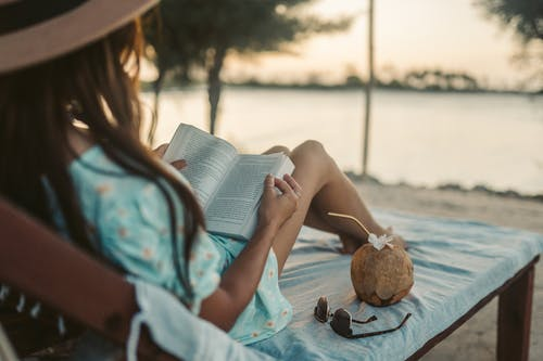 Selective Focus Photo of a Woman Reading a Book Beside a Coconut Drink and Sunglasses