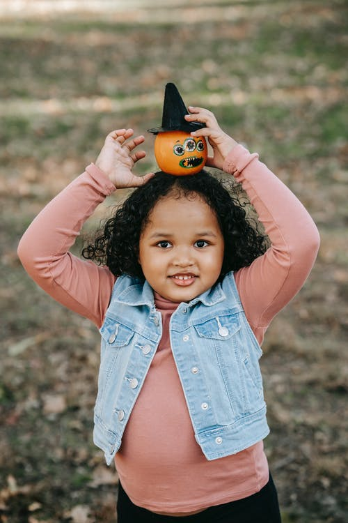 Happy little girl with pumpkin on head