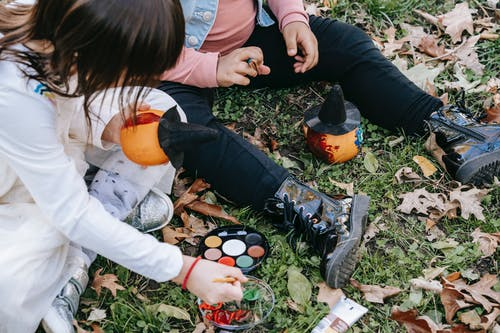 Crop children painting pumpkins in autumn park