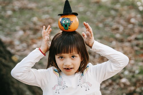 High angle of happy child in casual clothes standing in park with pumpkin on head and looking at camera