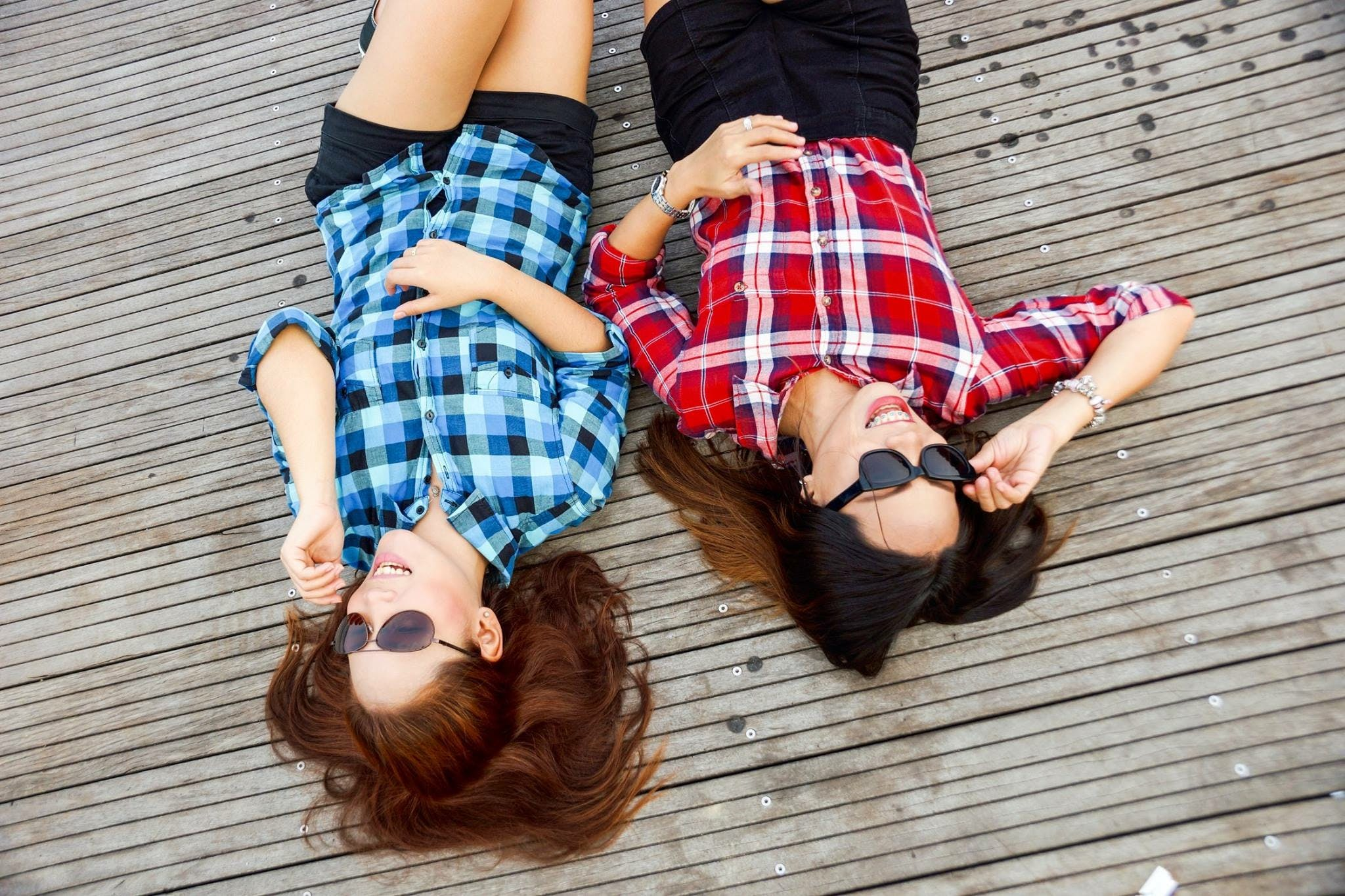 Two Woman Wearing Blue and Red Sport Shirts and Sunglasses Lying on Brown Surface