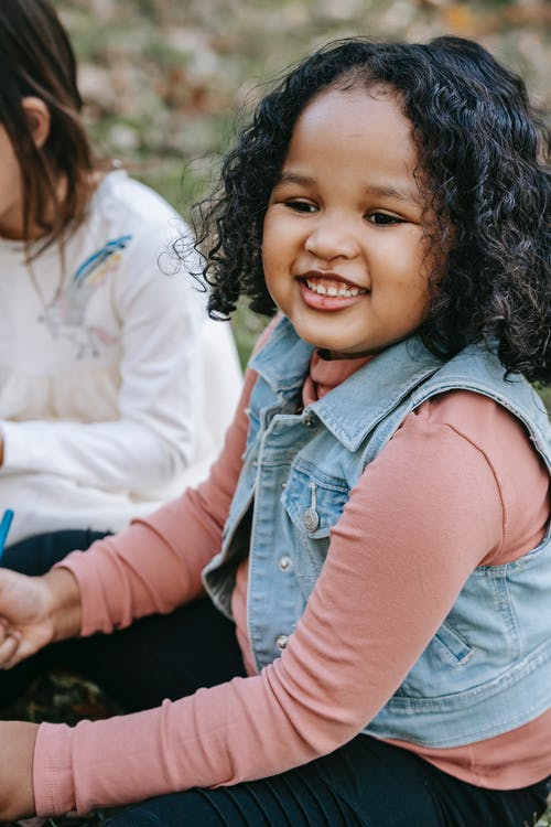 Cheerful black girl sitting in park with friend