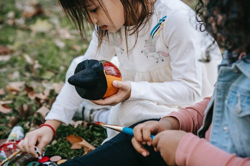 Concentrated multiethnic girls sitting on grass and painting pumpkin with brush and watercolors during Halloween holiday