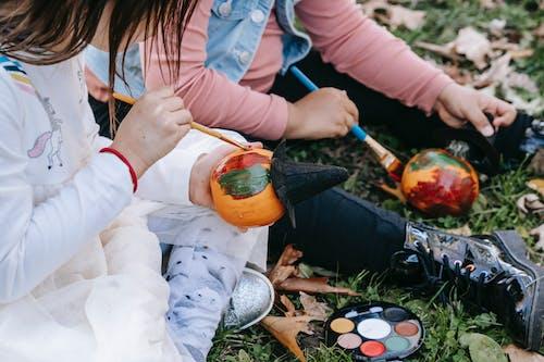 Little diverse girls decorating pumpkin with paint
