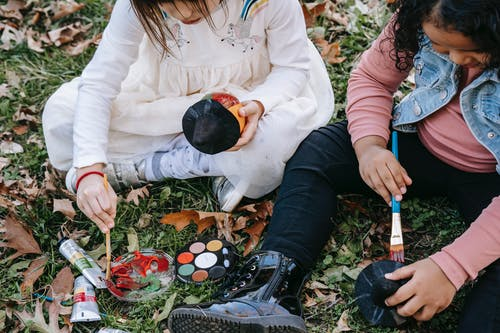 High angle of crop concentrated multiracial girls gathering on lawn and painting pumpkins for Halloween celebration