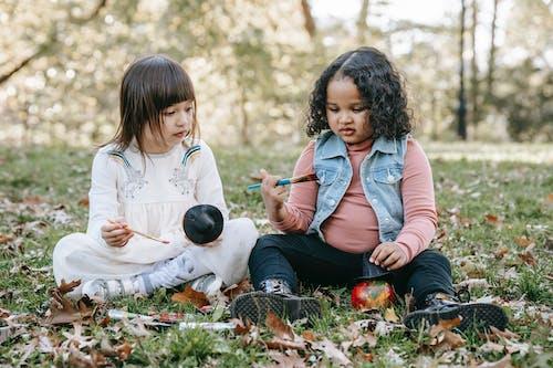 Diverse girls painting pumpkins in park