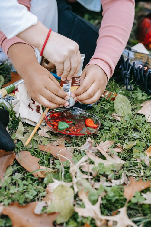Crop anonymous multiethnic friends preparing acrylic paints for painting sitting together on grass in park