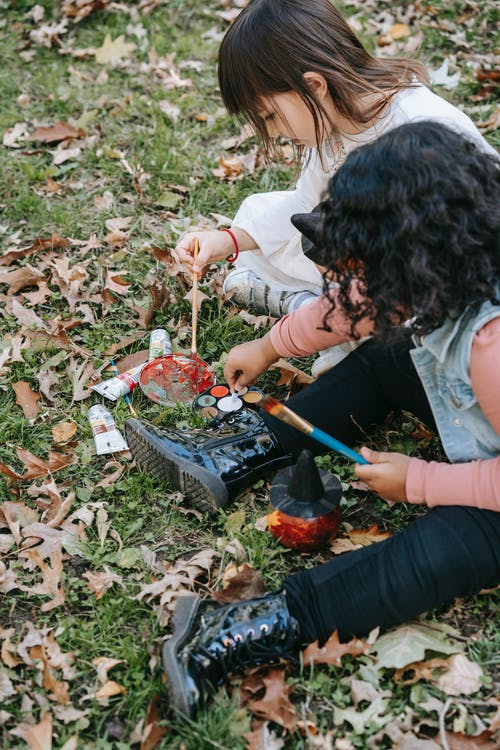Little diverse girls painting together with colorful paints