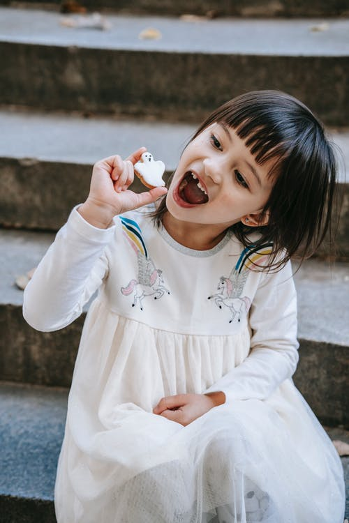 Funny expressive girl with mouth opened showing ghost cookie