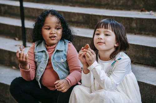 Cute diverse little girls eating delicious sweet cookies while sitting on stairs and spending weekend