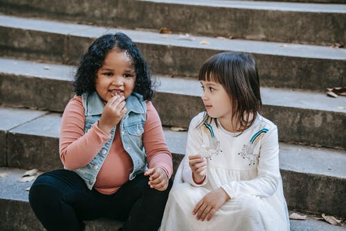 Cute diverse girls sitting together on stone stairs and eating delicious sweet cookies