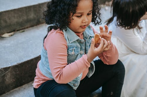 Black girl having gingerbread treat with friend