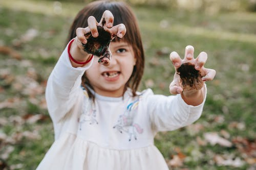 Funny girl with painted hands making scary face while playing in park during Halloween celebration