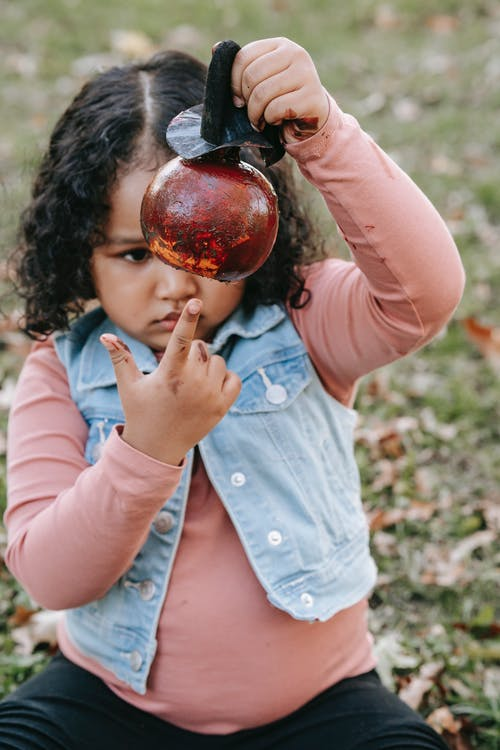 Cute black girl with painted pumpkin in park