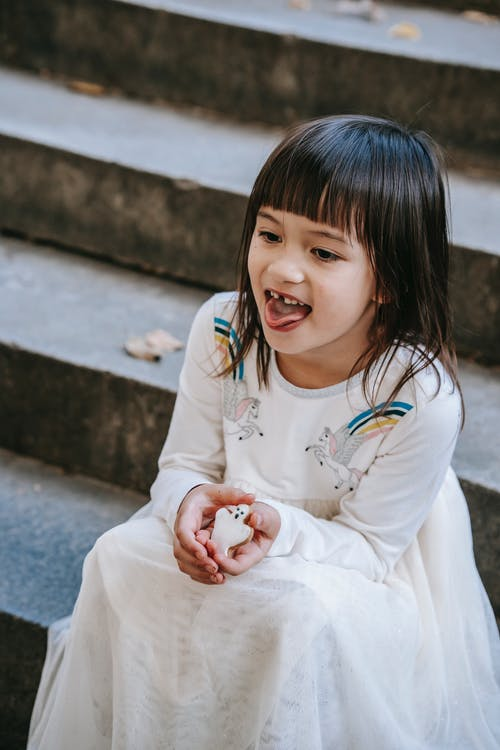 Funny girl in festive dress with sweet cookie
