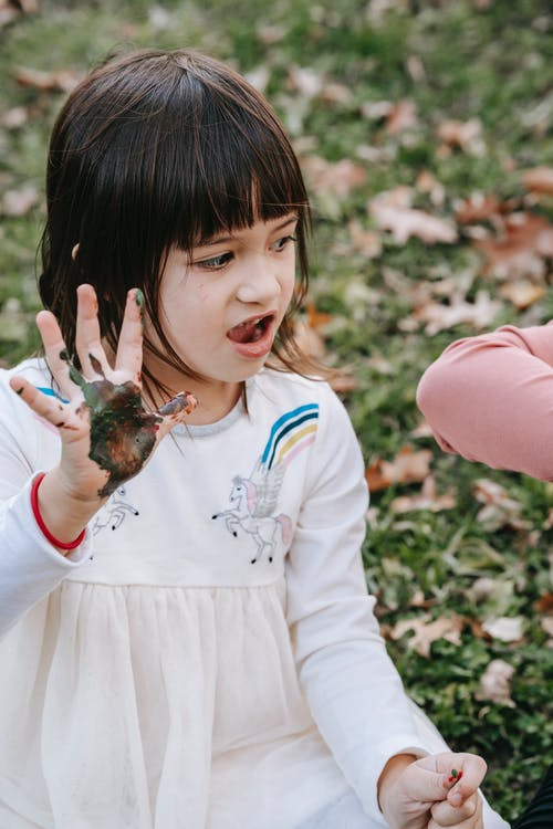 Cute little girl with mouth opened showing palm stained with paint while spending time with friend in park