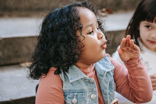 Side view of adorable little African American girl in casual clothes making faces
