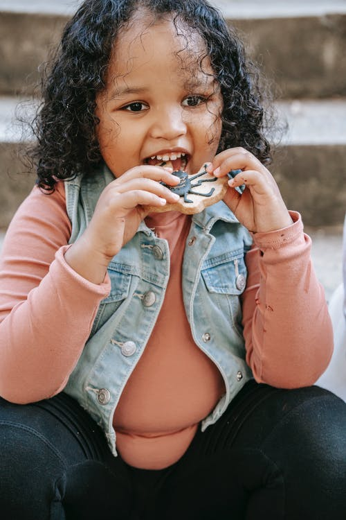 Happy cute African American little girl in casual outfit with curly hair eating yummy sweet cookie