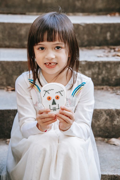 Cheerful little girl in white dress sitting on staircase with cookie decorated for Halloween as funny skull and looking at camera