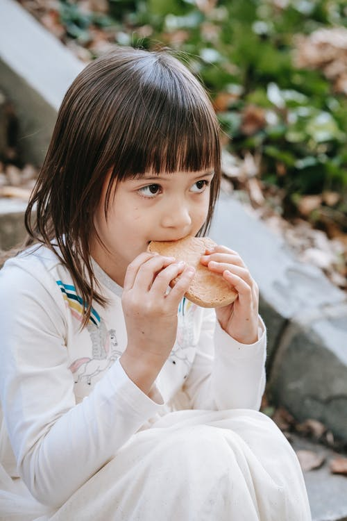 Hungry adorable girl with cookie