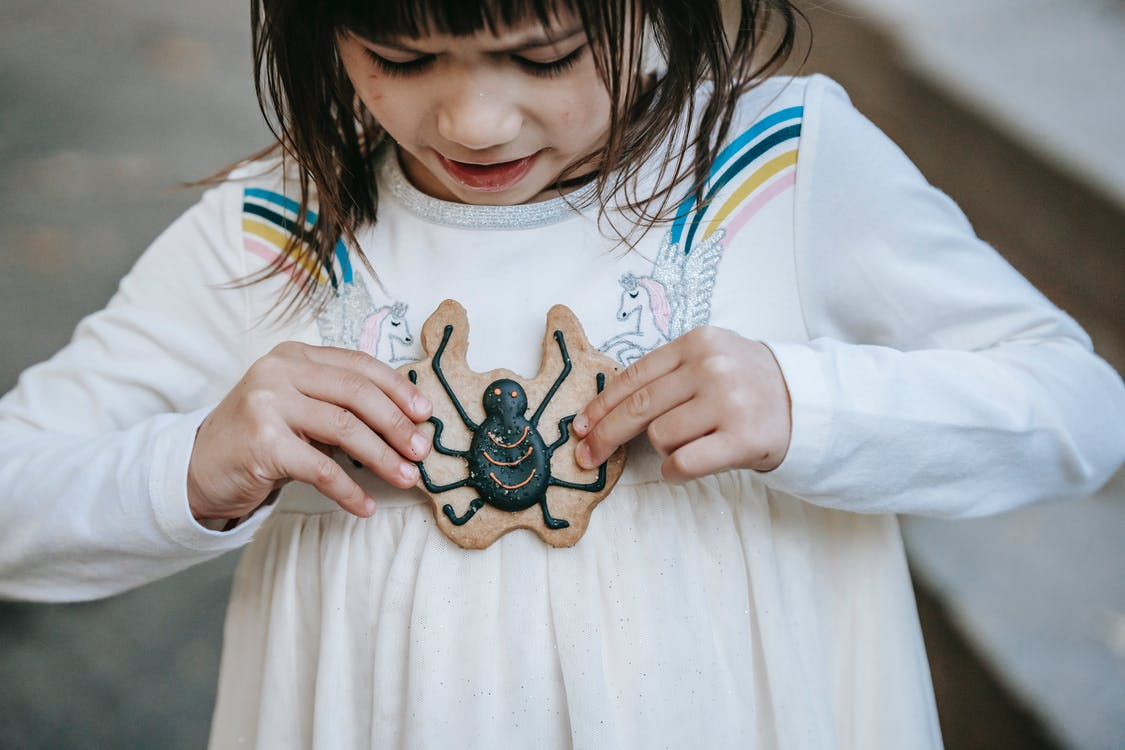 Little girl in white dress with fearful gaze with biscuit decorated with spider for Halloween