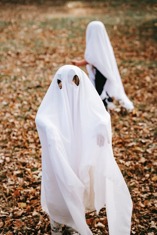 Faceless children in white outfits looking like mysterious ghosts playing in autumn park on Halloween