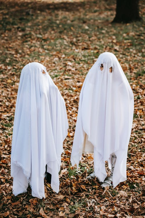 Playful children having fun in costumes of ghosts on Halloween in autumn park