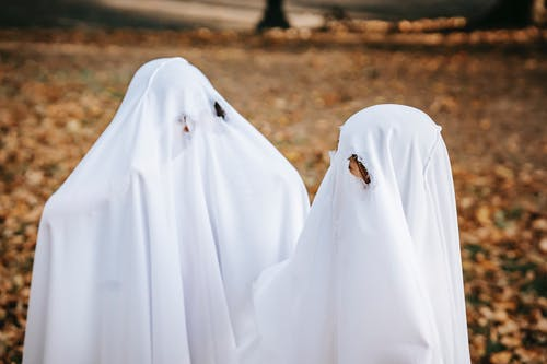 Faceless children playing ghosts in park