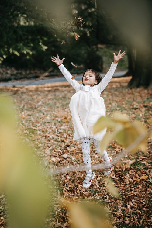 Happy little girl throwing leaves in park